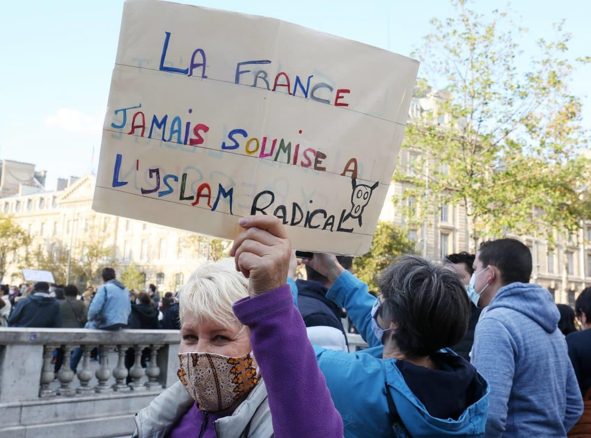 Nainen pitelee kylttiä, jossa lukee, ettei Ranska koskaan alistu islamismille.