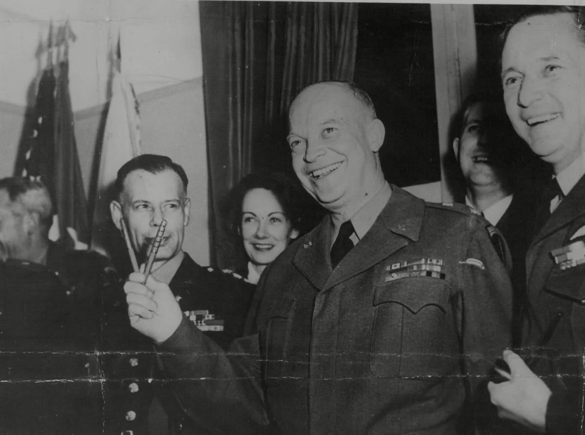 Eisenhower pitää kahta kynää kädessään v-muodossa