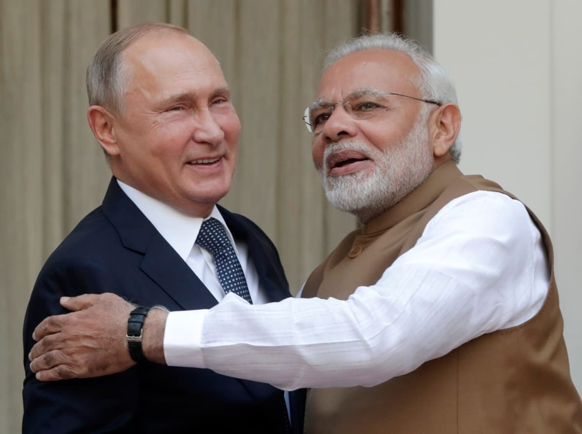 Ruskea liivinen mies pitää kättään hymyilevän sinitakkisen miehen ympärillä.
