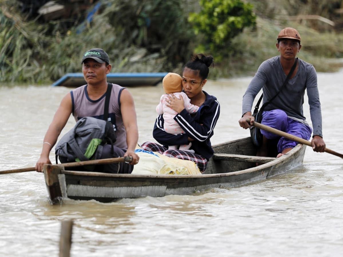 Kolme ihmistä pienessä veneessä, veneen etu- ja takaosassa istuvat lippalakkipäiset miehet soutavat, keskellä istuu nainen vauva sylissään.