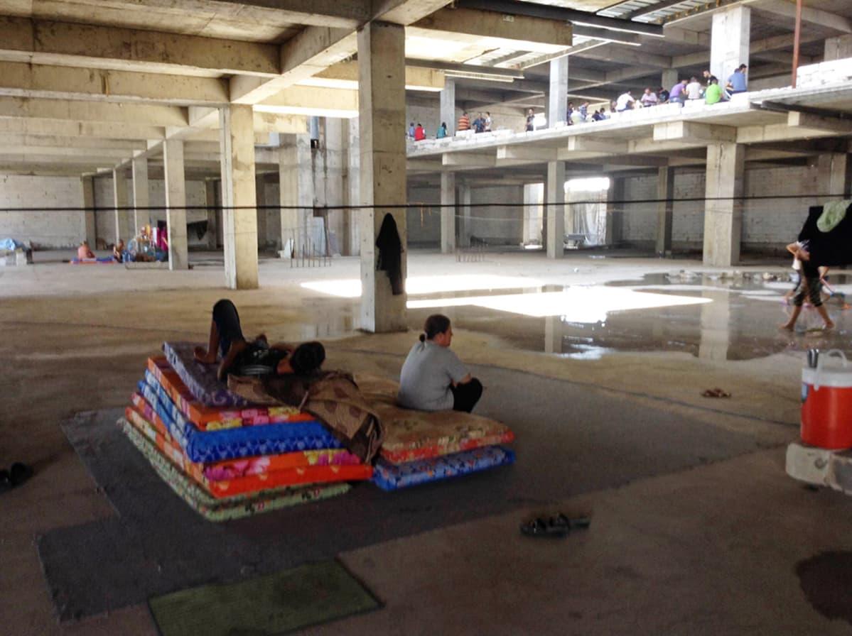 Pakolaisia keskeneräisen kerrostalon pohjakerroksessa.