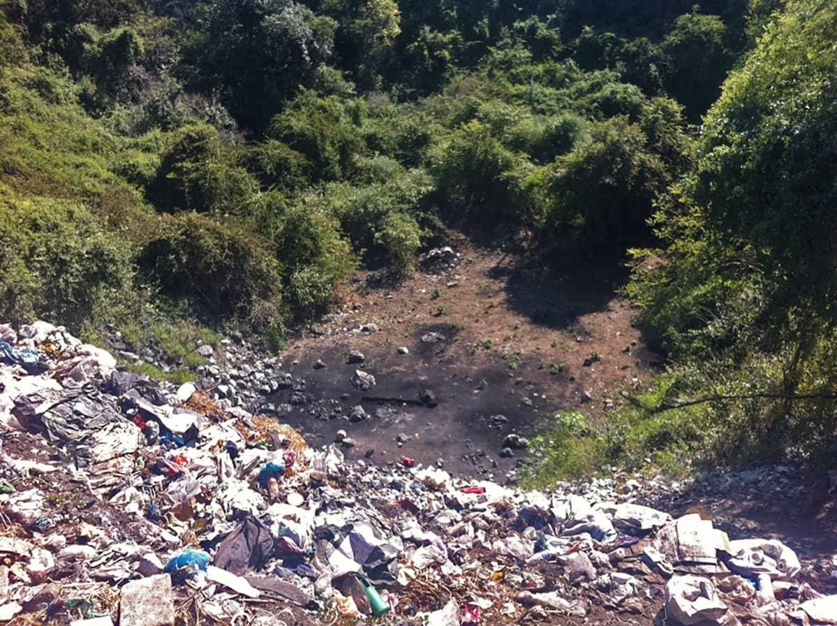 Tapetut opiskelijat viskattiin tälle kaatopaikalle - rikolliset sanovat polttaneensa heidät tuolla alhaalla, missä näkyy mustunut maa-alue.