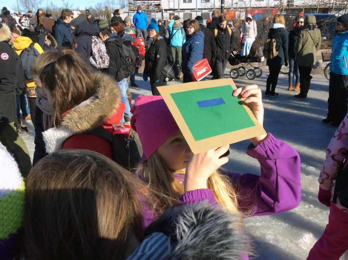 Ihmisiä Oulun torilla katsomassa auringonpimennystä.