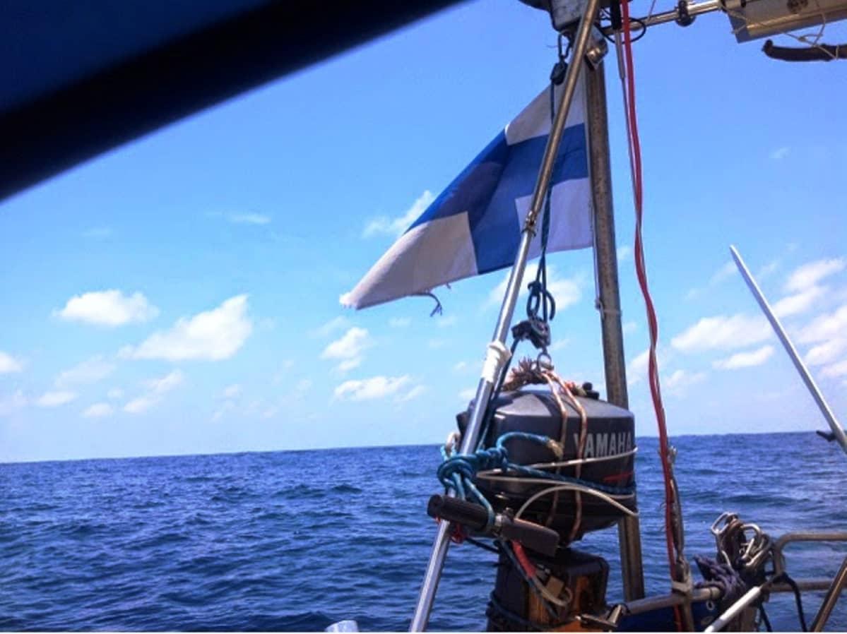 Suomenlippu veneessä ja taustalla aava meri