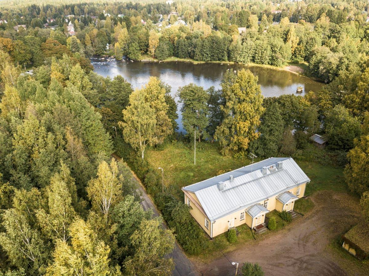 Ilmakuva Kyminlinnan komendantintalosta Kymijoen varressa metsittyneen maiseman ympäröimänä.