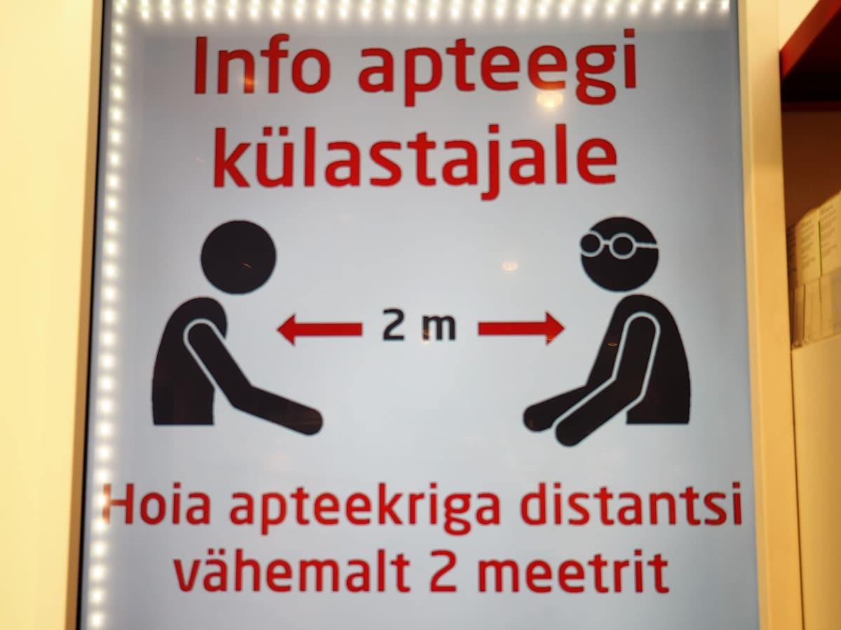 Tallinnalaisen apteekin kyltti muistuttaa, että työntekijään on pidettävä vähintään kahden metrin etäisyys.