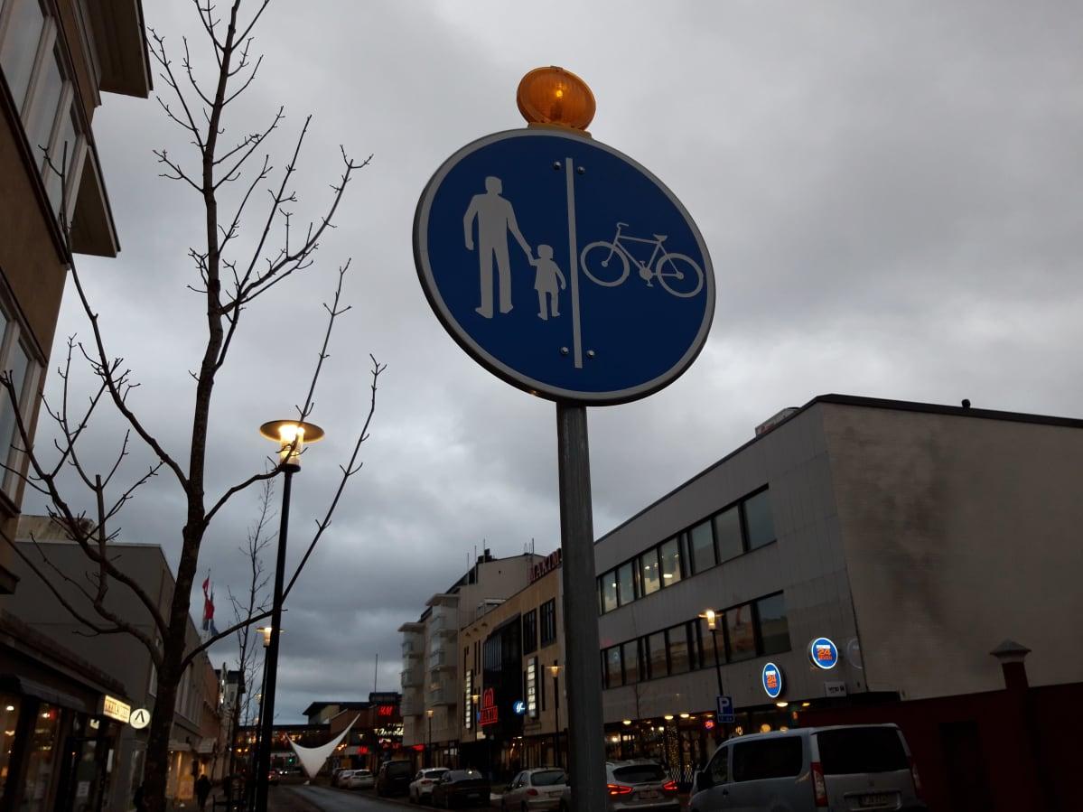 Kevyen liikenteen väylän merkki, jonka yhteydessä myös vilkkuvalo.