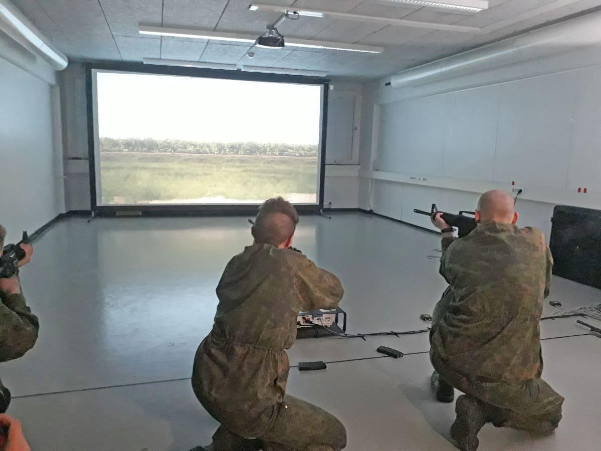 Varusmiehet harjoittelevat ampumista valkokankaan edessä.