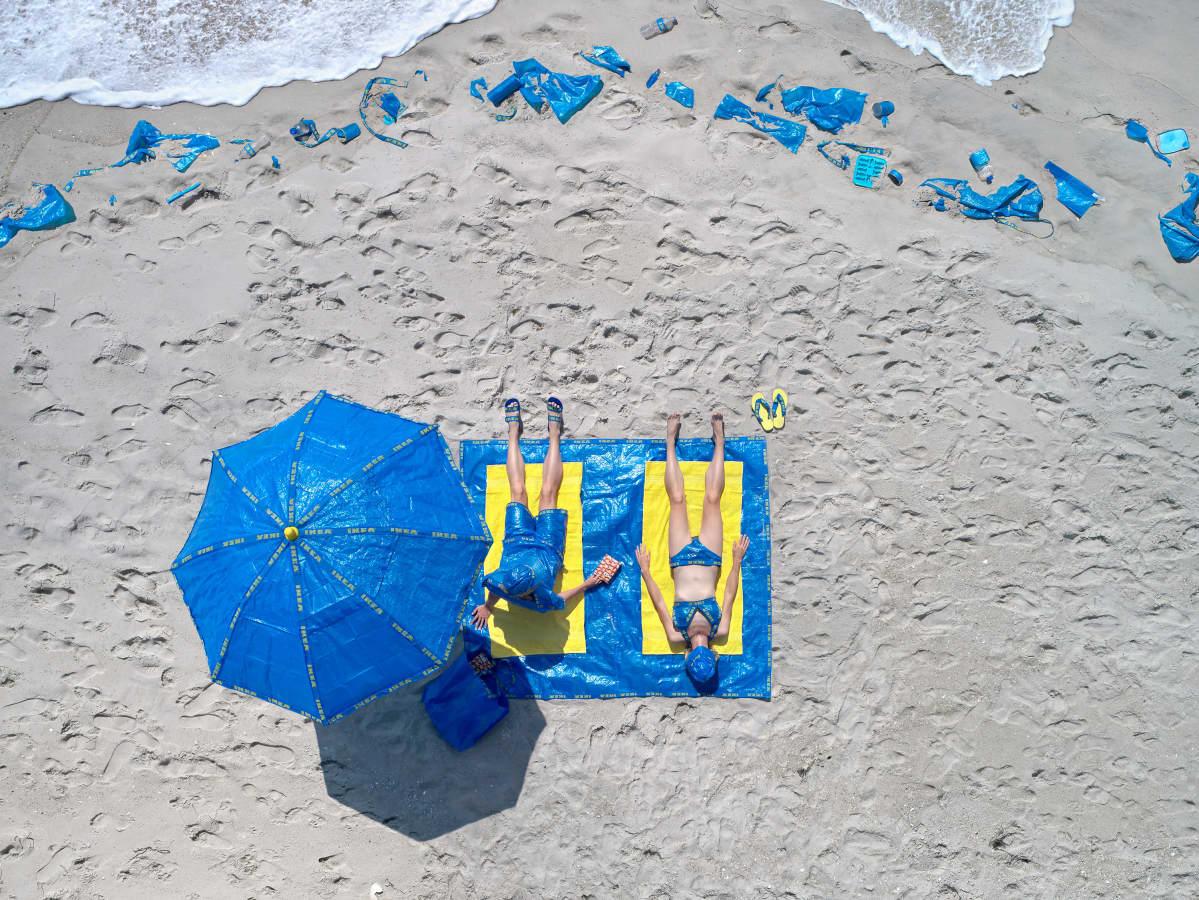 Valokuvateos, jossa Ikea-kasseja auringonvarjoina ja pyyhkeenä käyttävät kaksi ihmistä makaavat rannalla. Rannalla näkyy Ikea-kasseja hiekan seassa.