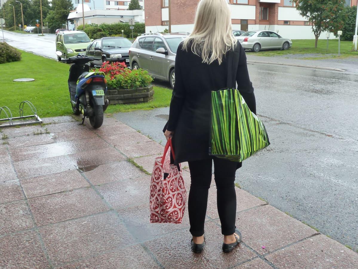 Nainen seisoo kadulla kestokassit käsissään.