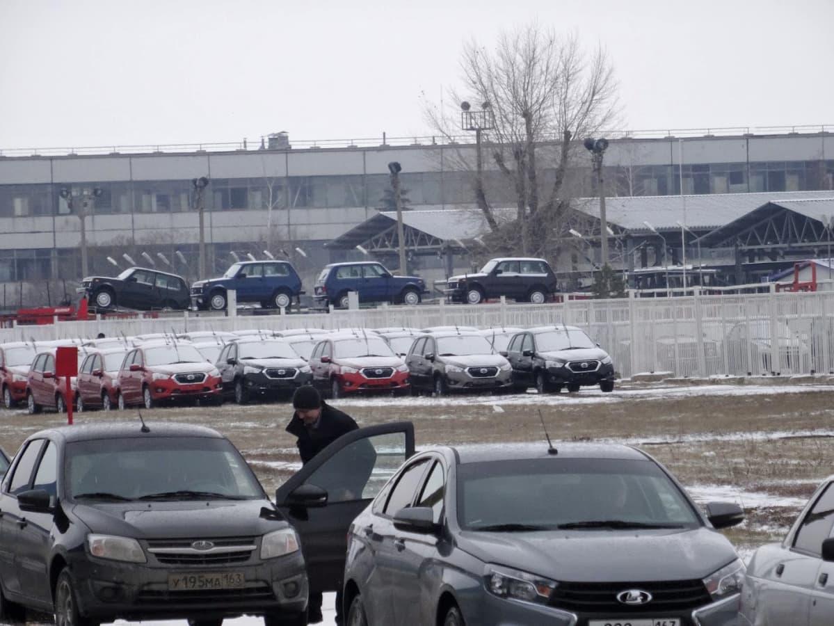 Tehtaan pihalla seisoo autoja valmiina markkinoille.