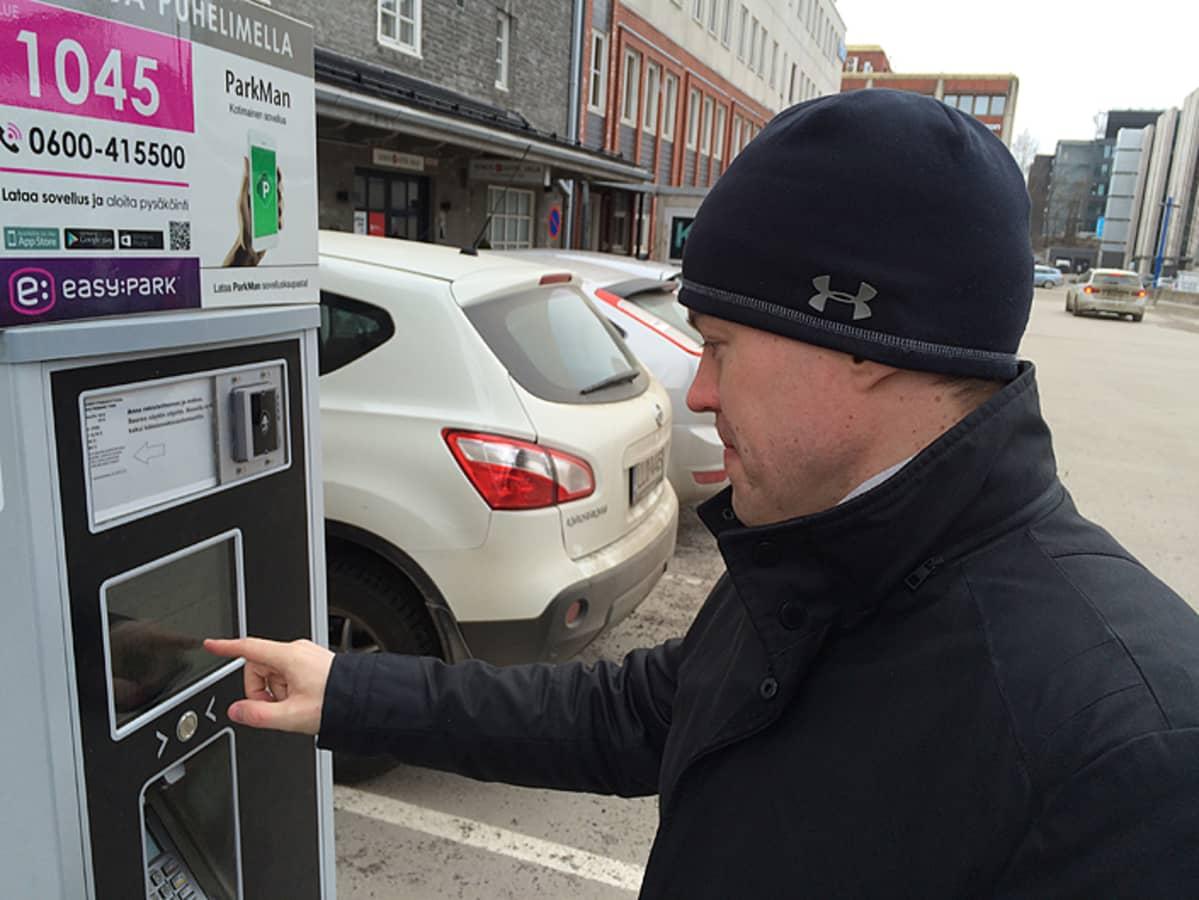 Mies pysäköintiautomaatilla.