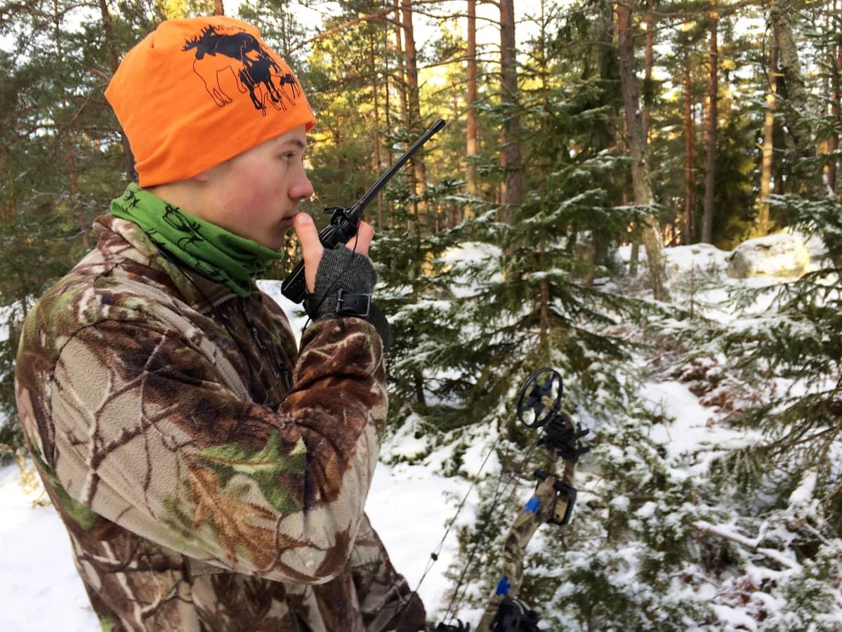 Metsästäjä puhuu radiopuhelimeen metsässä.