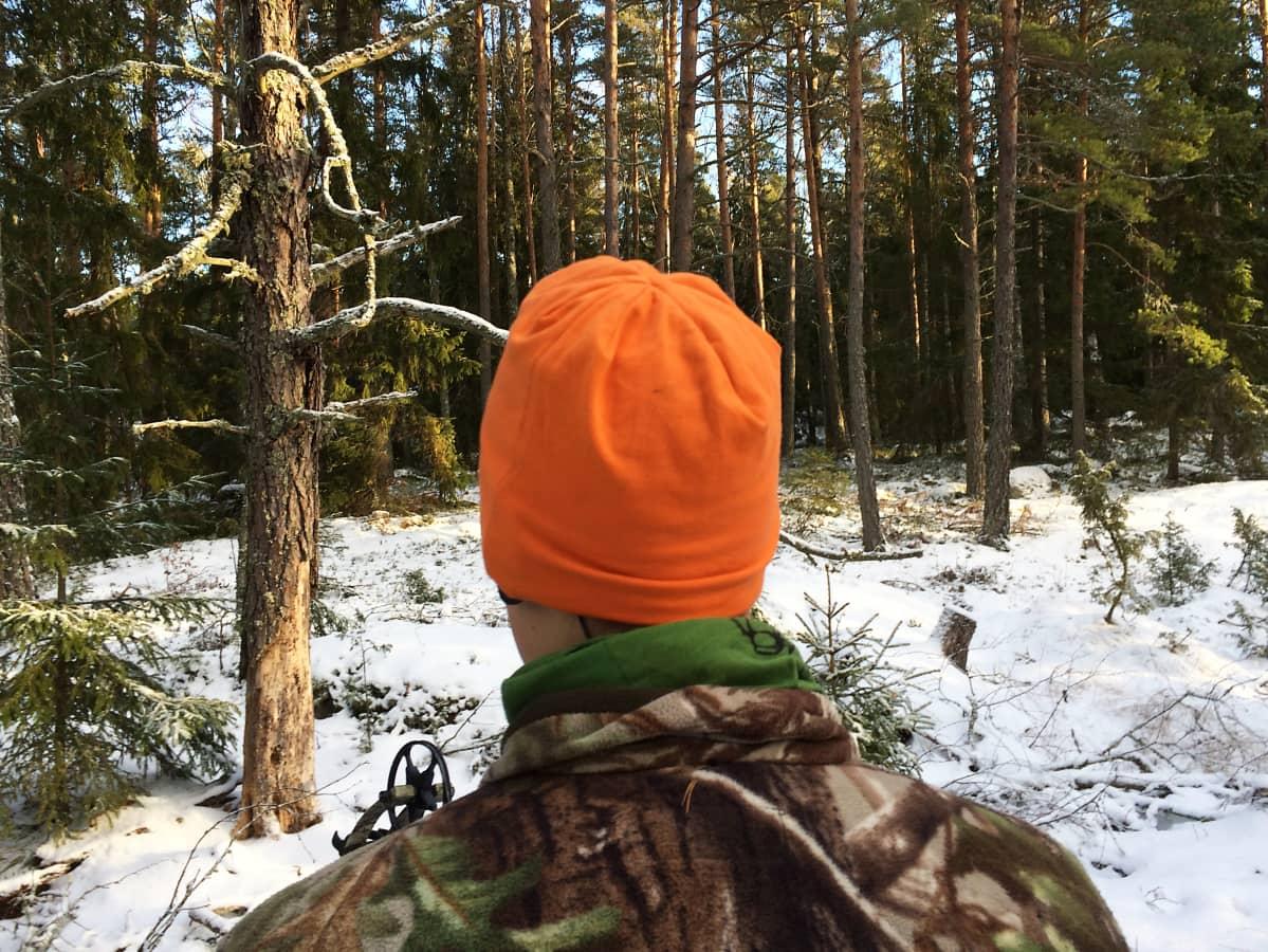 Metsästäjä seisoo metsässä.