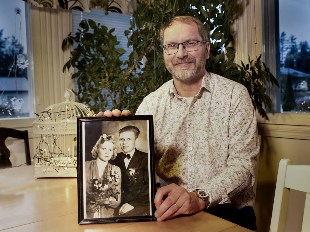 Mika Koivunen istuu pöydän äärellä, katsoo kameraan hymyillen ja pitelee vanhempiensa hääkuvaa.