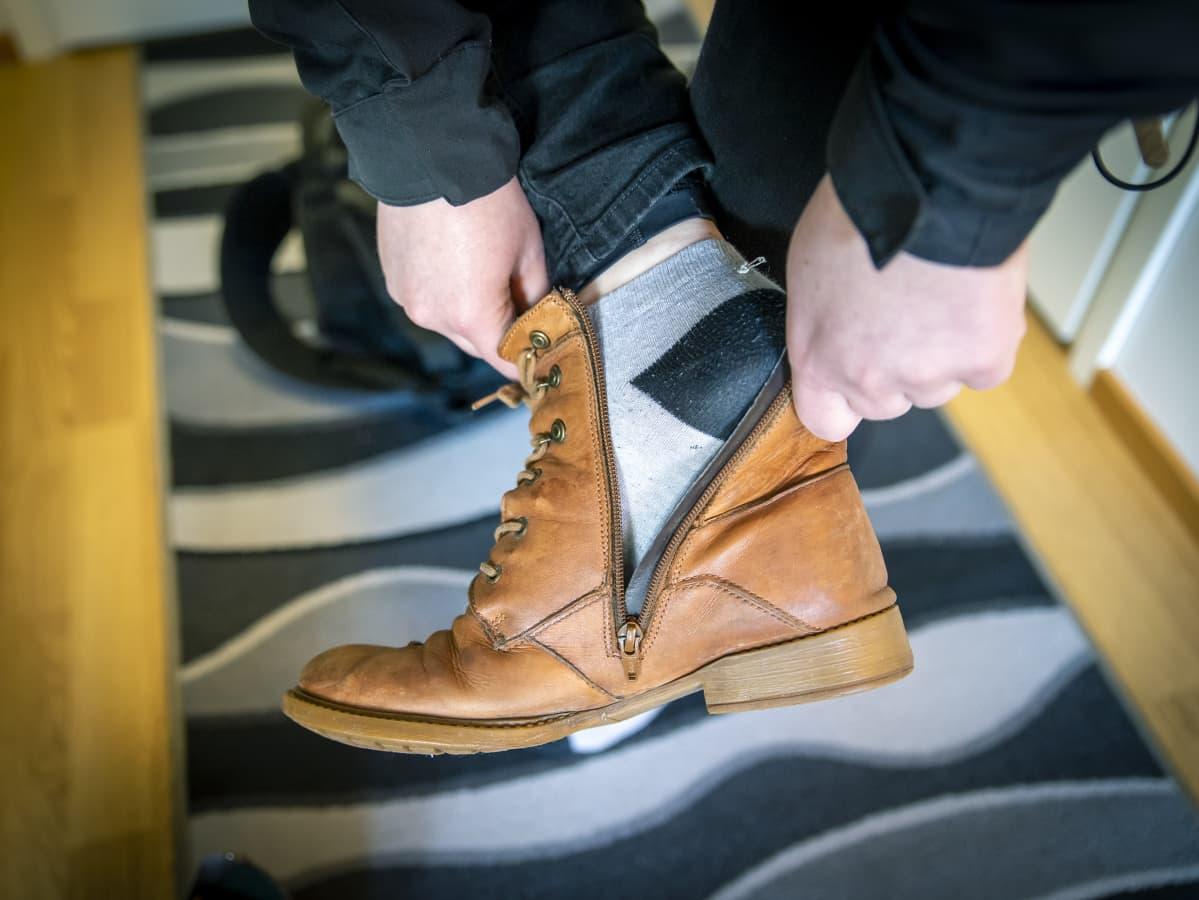 Helena Salo laittaa kenkää jalkaan.