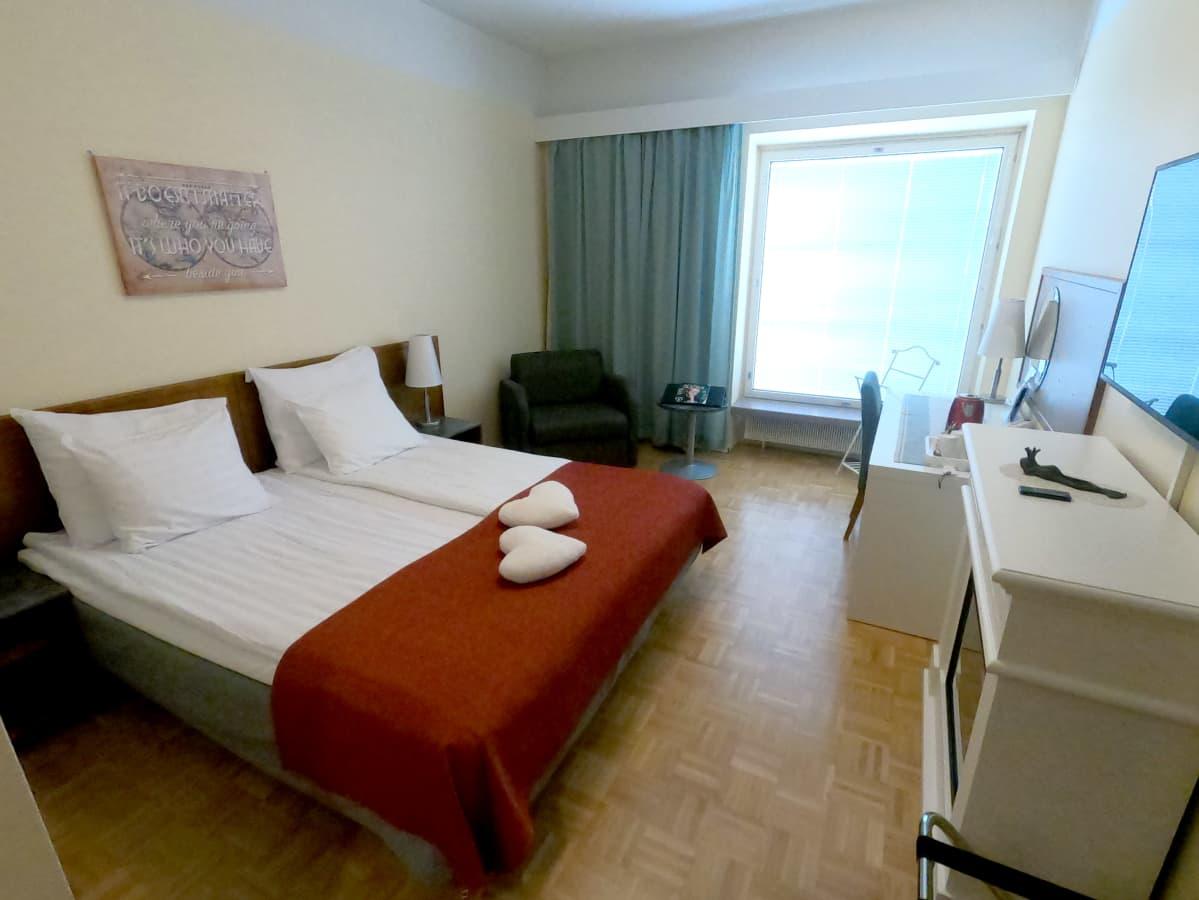 hotelli huone jossa sängyllä sydän tyynyt