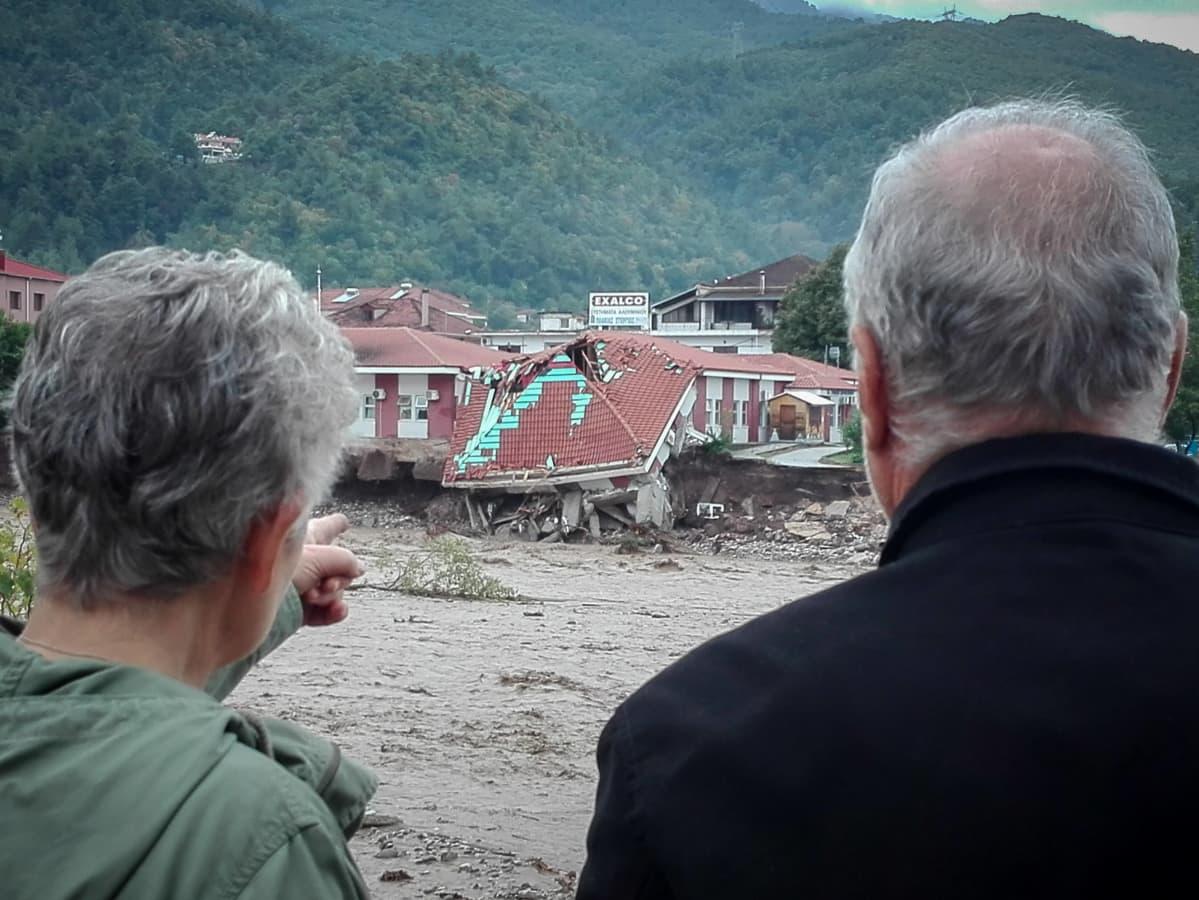 Nainen ja mies katsovat tuhoutuneita rakennuksia.