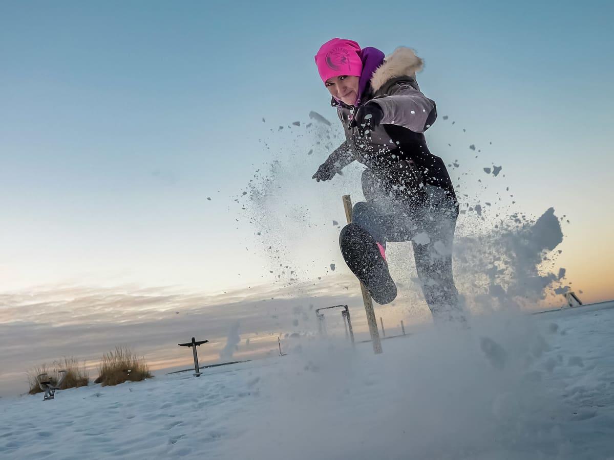 Oululainen Netta Brandt potkaisee lunta kameraa kohti