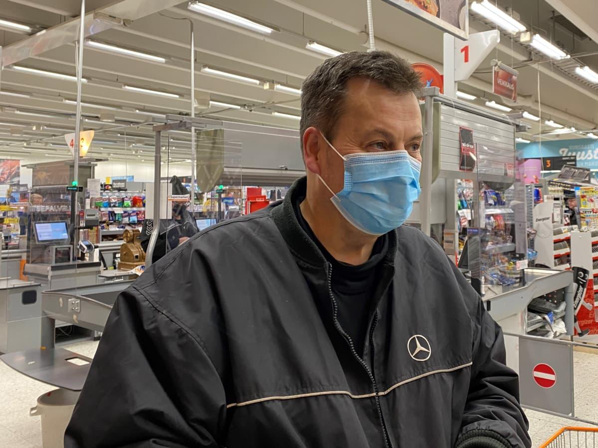 Olavi Kortelainen seisoo Siilinjärven K-Supermarketin kassojen edessä.