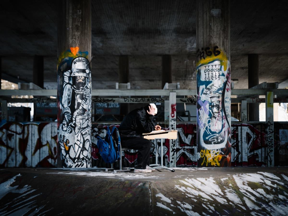 kuvituskuva nuori istuu yksin pulpetin ääressä graffitien ympäröimänä