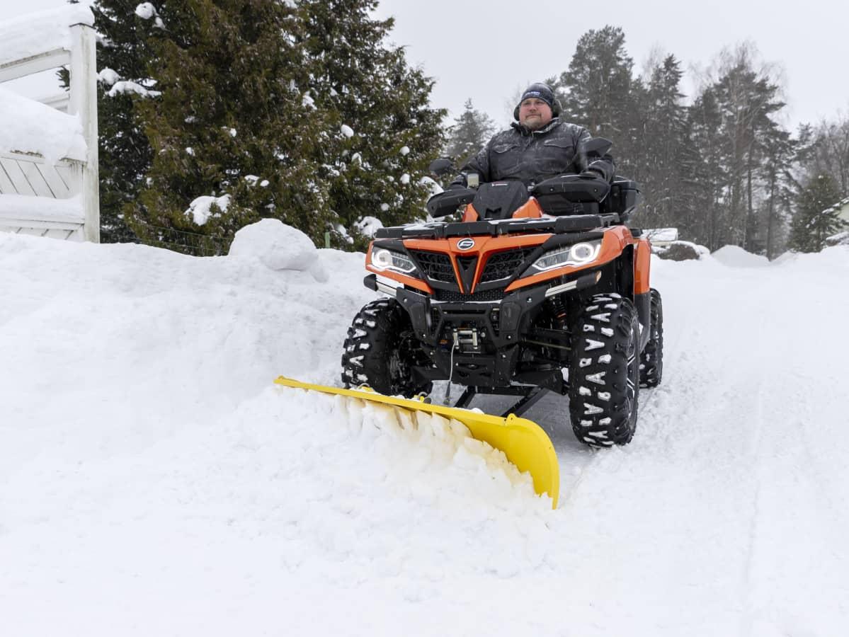 Mies auraa mönkijällä lunta.