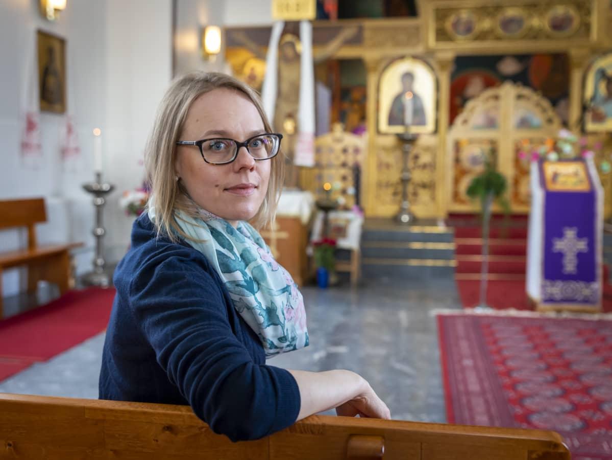 Elina Ruuttila istuu kirkon penkissä.