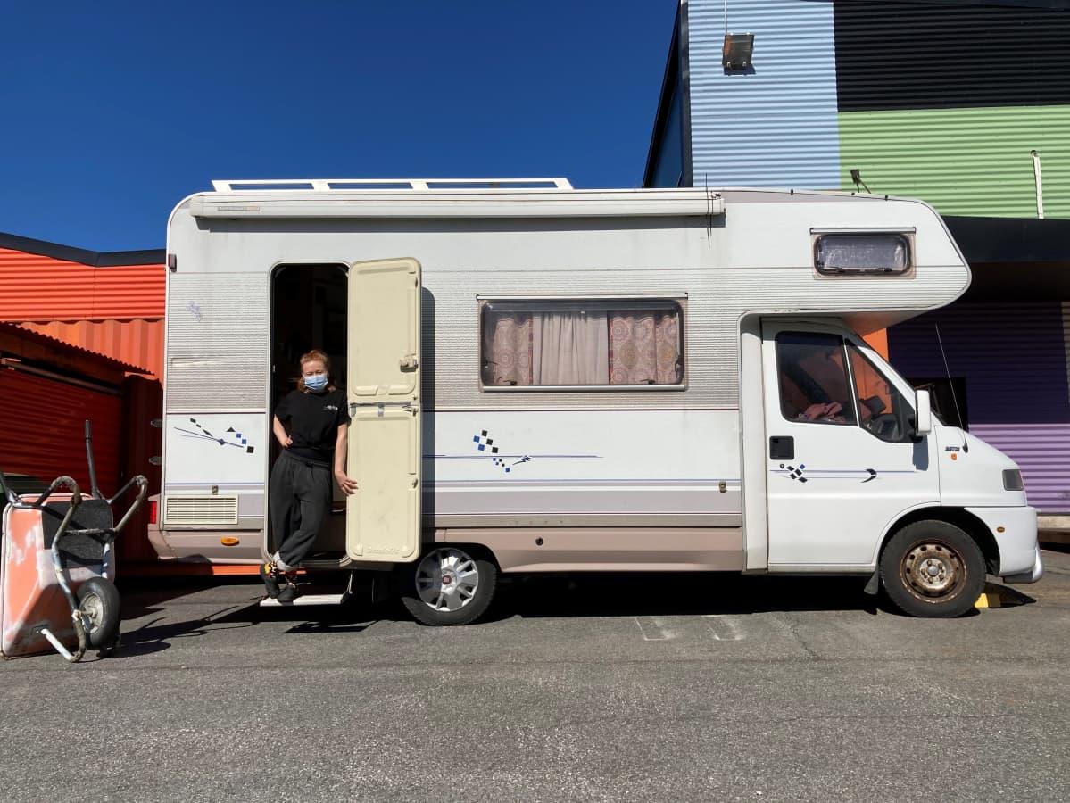 Rosa-Maria Autio asuntoautonsa ovella kevätauringossa. Taustalla näkyy värikästä seinää.