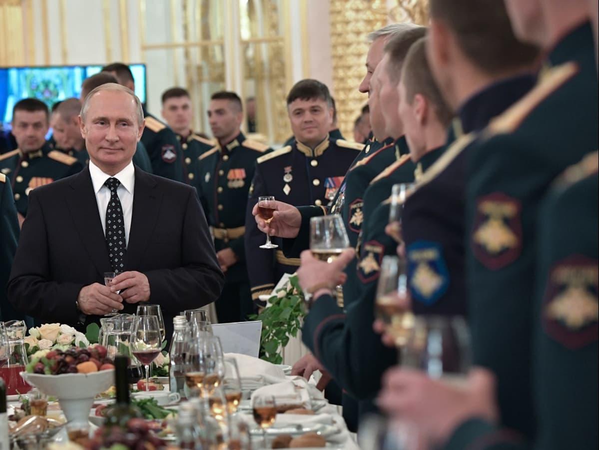 Putin seisoo sampanjalasi kädessään tummassa puvussa pöydän päässä. Pöydän ääressä ja taustalla näkyy sotilashenkilöitä juhlaunivormuissa lasit käsissään.