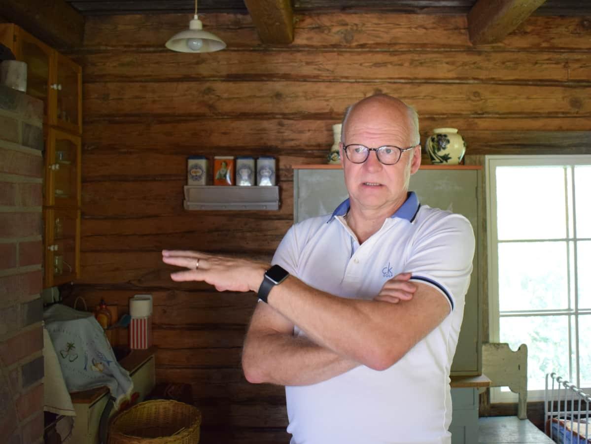 Reijo Karhinen yhden kokoamansa hirsitalon sisäsllä.