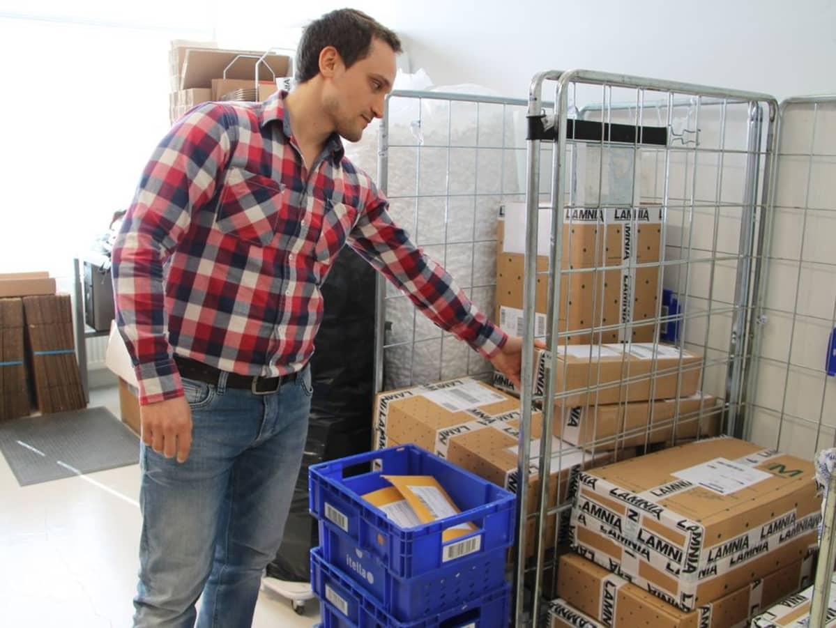 Lamnian omistaja Mihail Pinhasov tarkastelee maailmalle lähteviä tuotepaketteja.