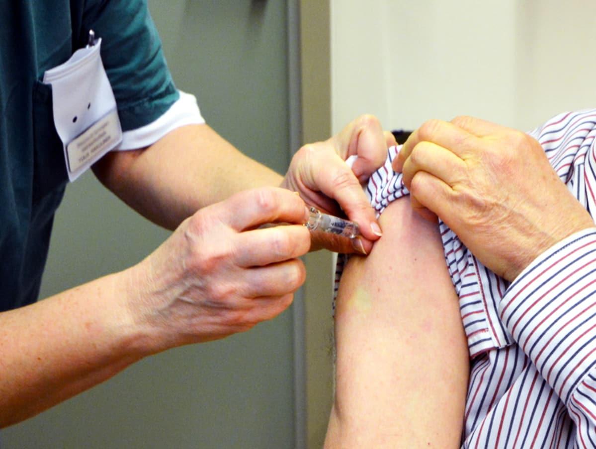 Hoitaja antaa rokotetta.