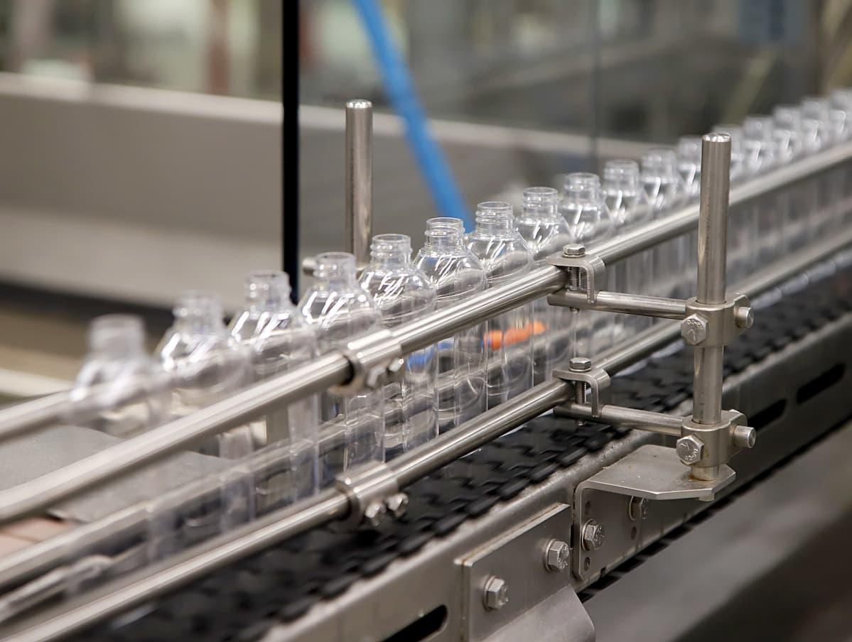 Tyhjiä käsihuuhdepulloja tuotantolinjalla.