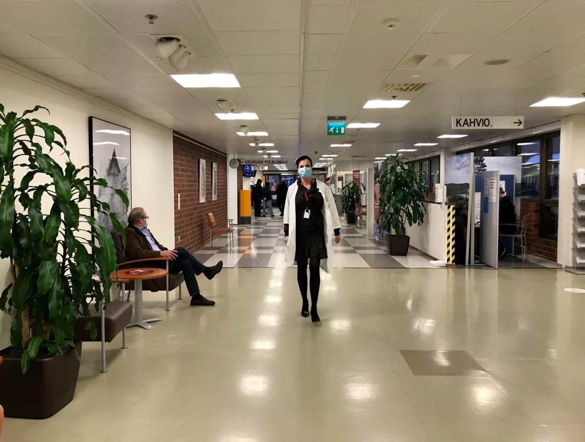 Lääkäri kävelee sairaalan aulassa maski naamassa, päällä lääkärintakki ja jalassa korkokengät.