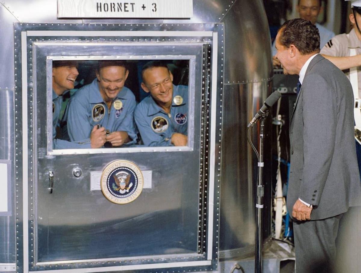 Arnstrong, Collins ja Aldrin kurkistevat hymyillen karanteenihuoneen ikkunasta, jonka edessä seisoo Nixon.