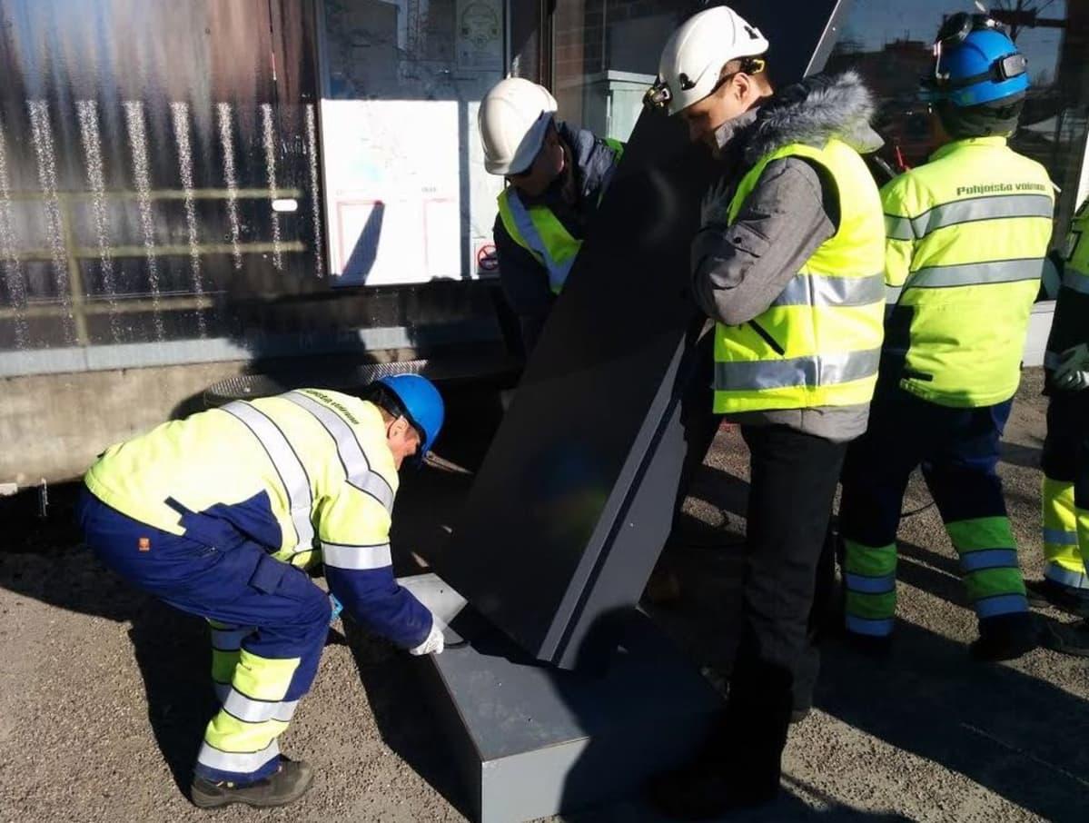 Uutta näyttöä asennetaan bussipysäkille Oulussa.