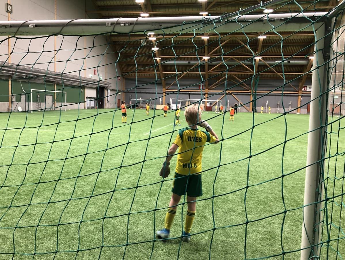 Poika seisoo jalkapallomaalilla odottamassa maalipotkua