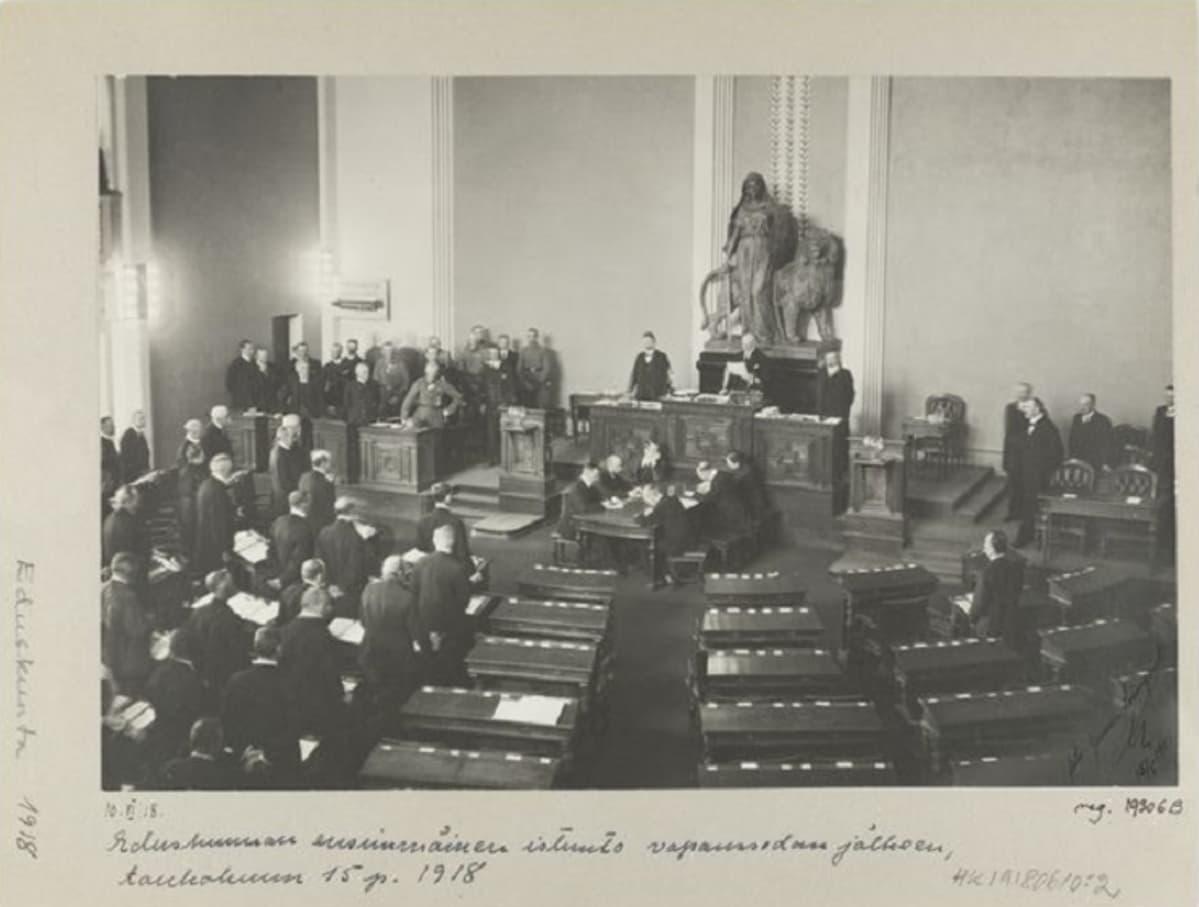 Mustavalkoinen  kuva eduskunnasta, jonka toisen puolikkaan istuimet ovat tyhjä yhtä miestä lukuun ottamatta.