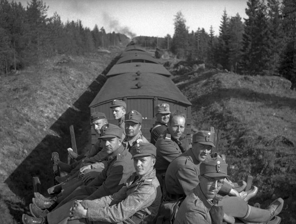 9 sotilasta istuu selät vastakkain junan katolla matkalla sotaan.