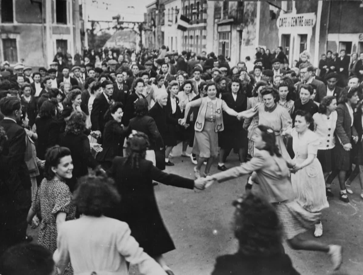 Naiset tanssivat piirissä ihmisjoukon keskellä.