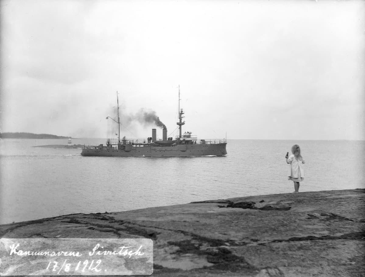 Tyttö katsoo merellä lipuvaa sotalaivaa