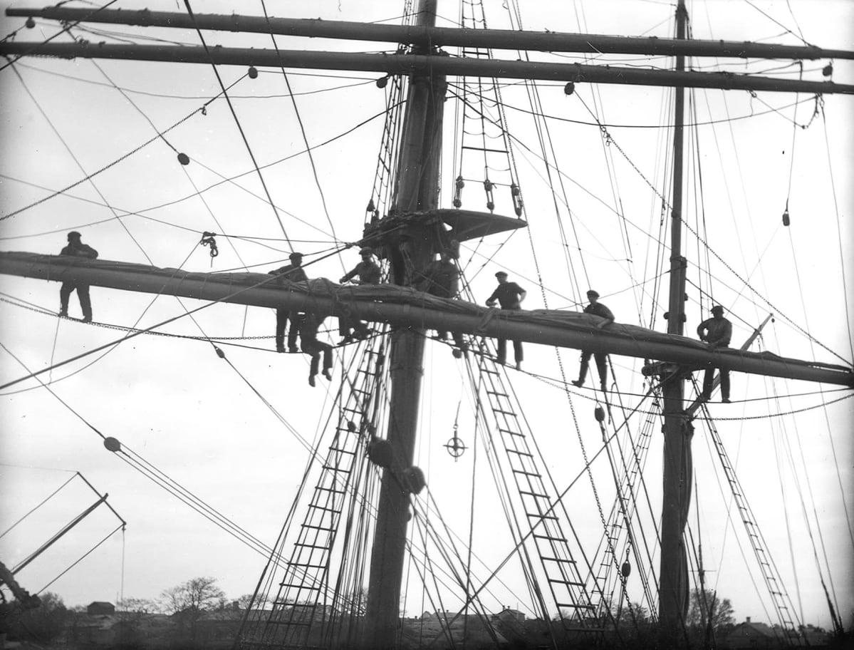 Miehiä purjelaivan raakapuulla