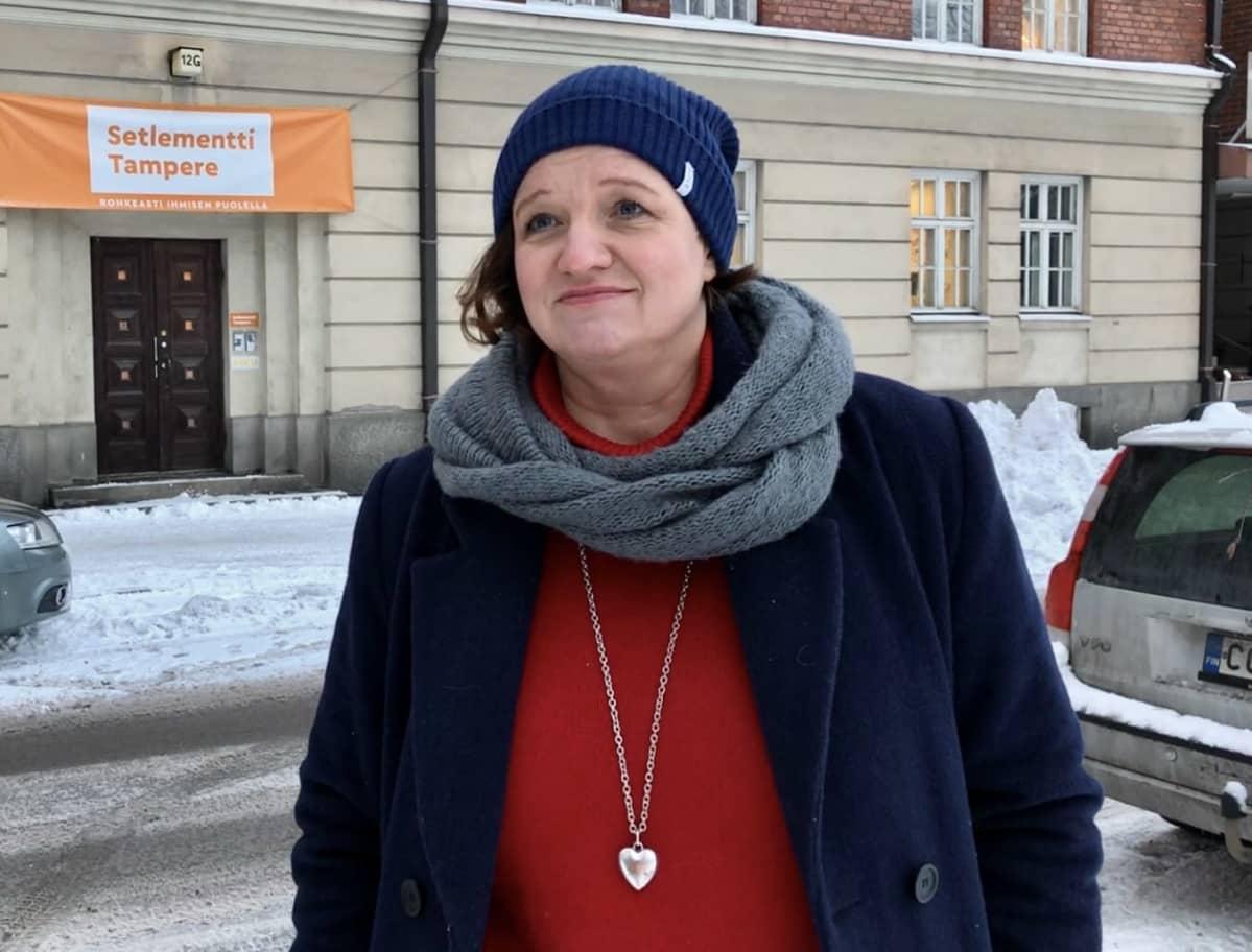 Tampereen Setlementin kriisityöntekijä Mari McAlester seisoo työpaikkansa edessä.