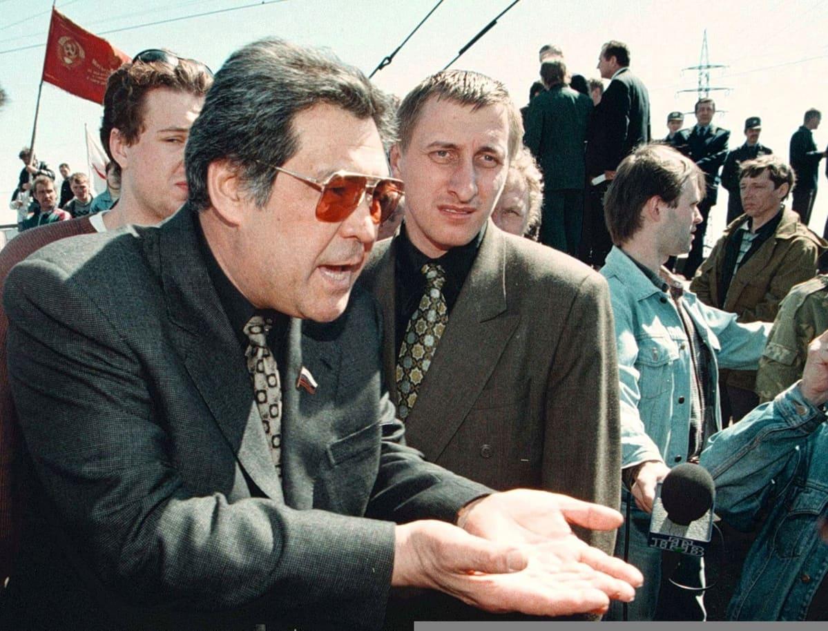 Tummassa puvussa ja tummissa laseissa oleva Tulejev puhuu viittilöiden käsillään. Ympärillä on pukumiehiä, taustalla näkyy punainen lippu.