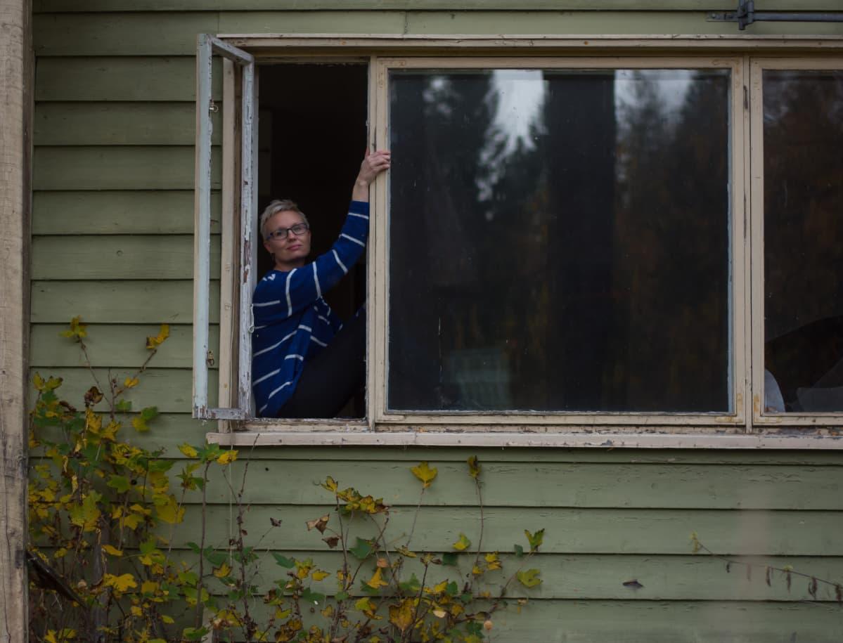 Nainen istuu ränsistyneen puutalon ikkunanlaudalla ja katsoo kameraa kohti.
