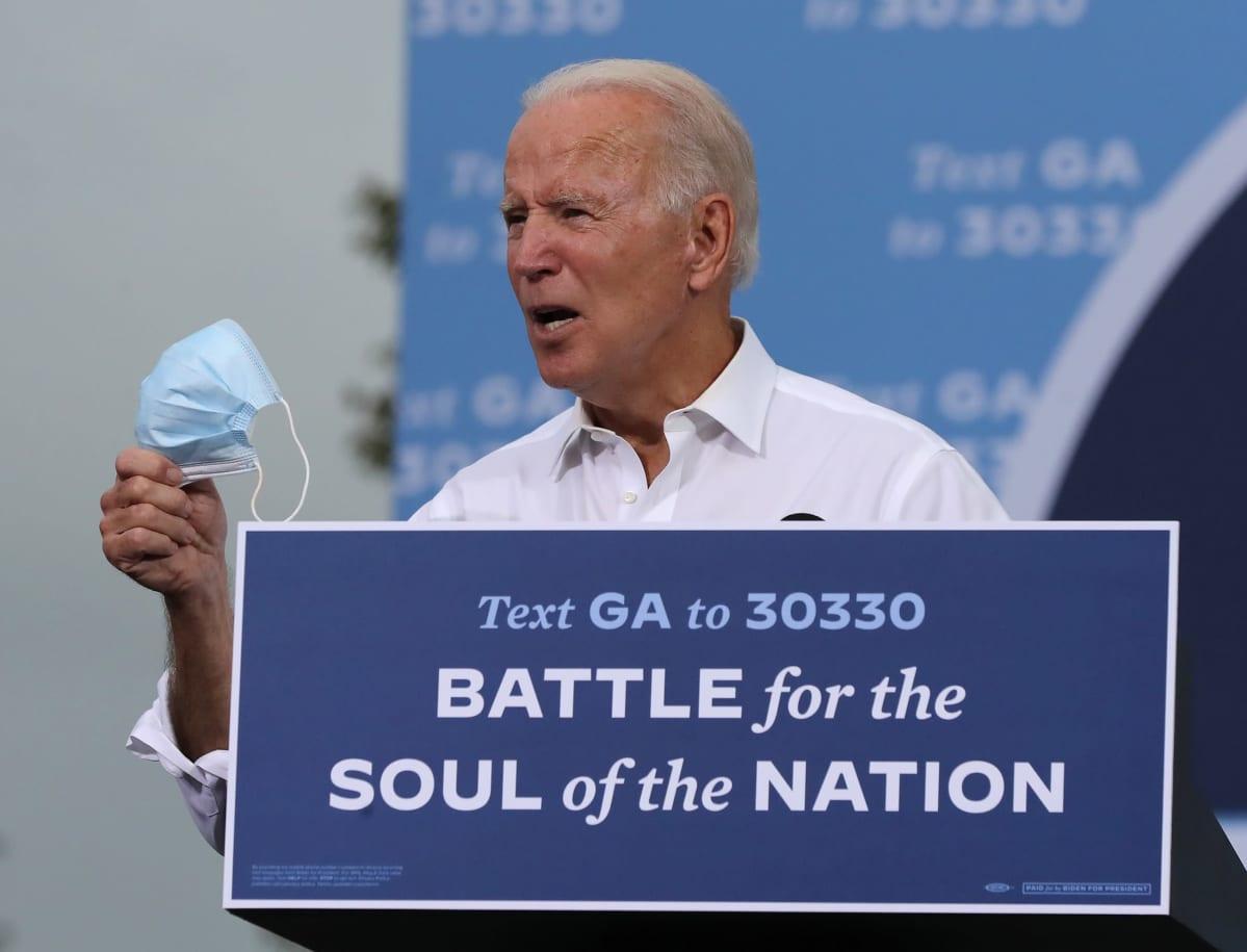 Joe Biden puhuu kannattajilleen. Hänellä on oikeassa kädessä kasvomaski.