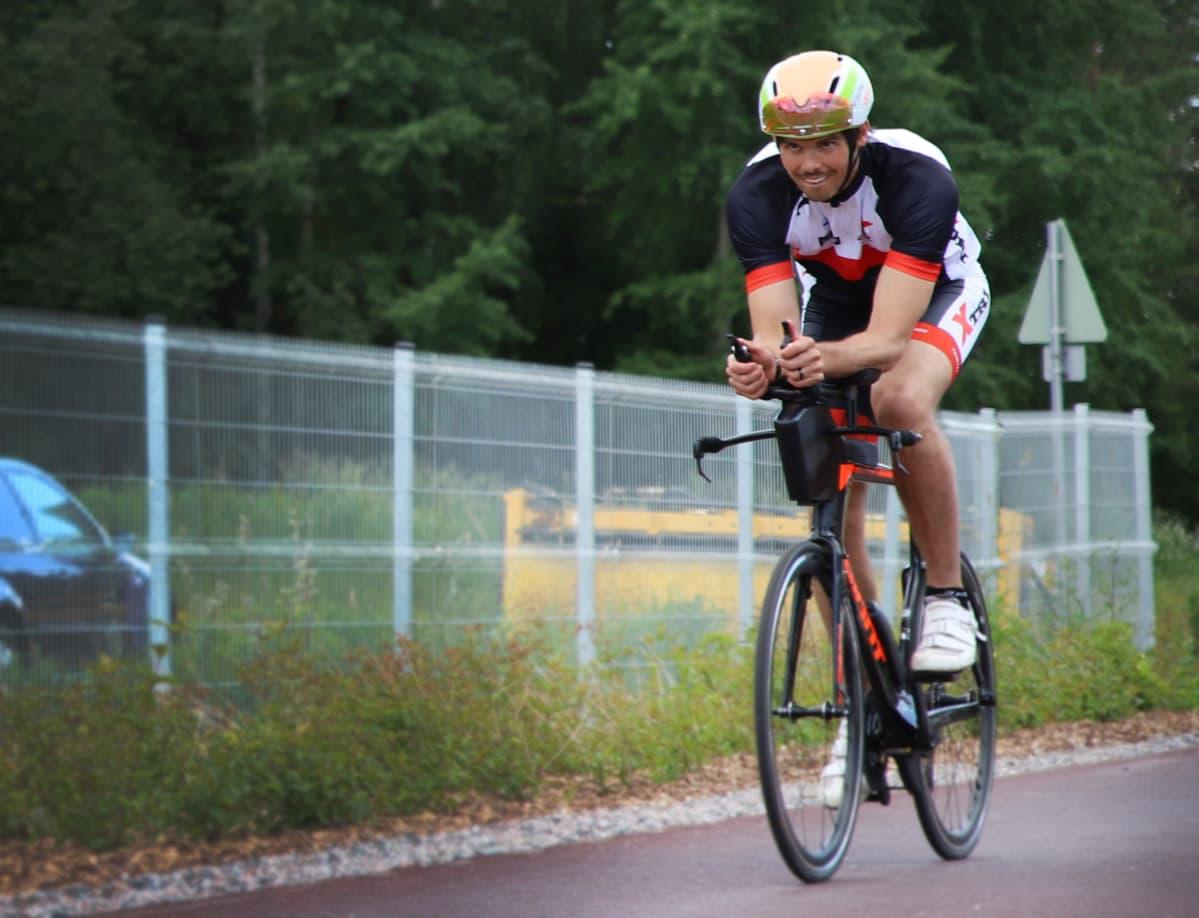 Mies polkee triathlonpyörällä.