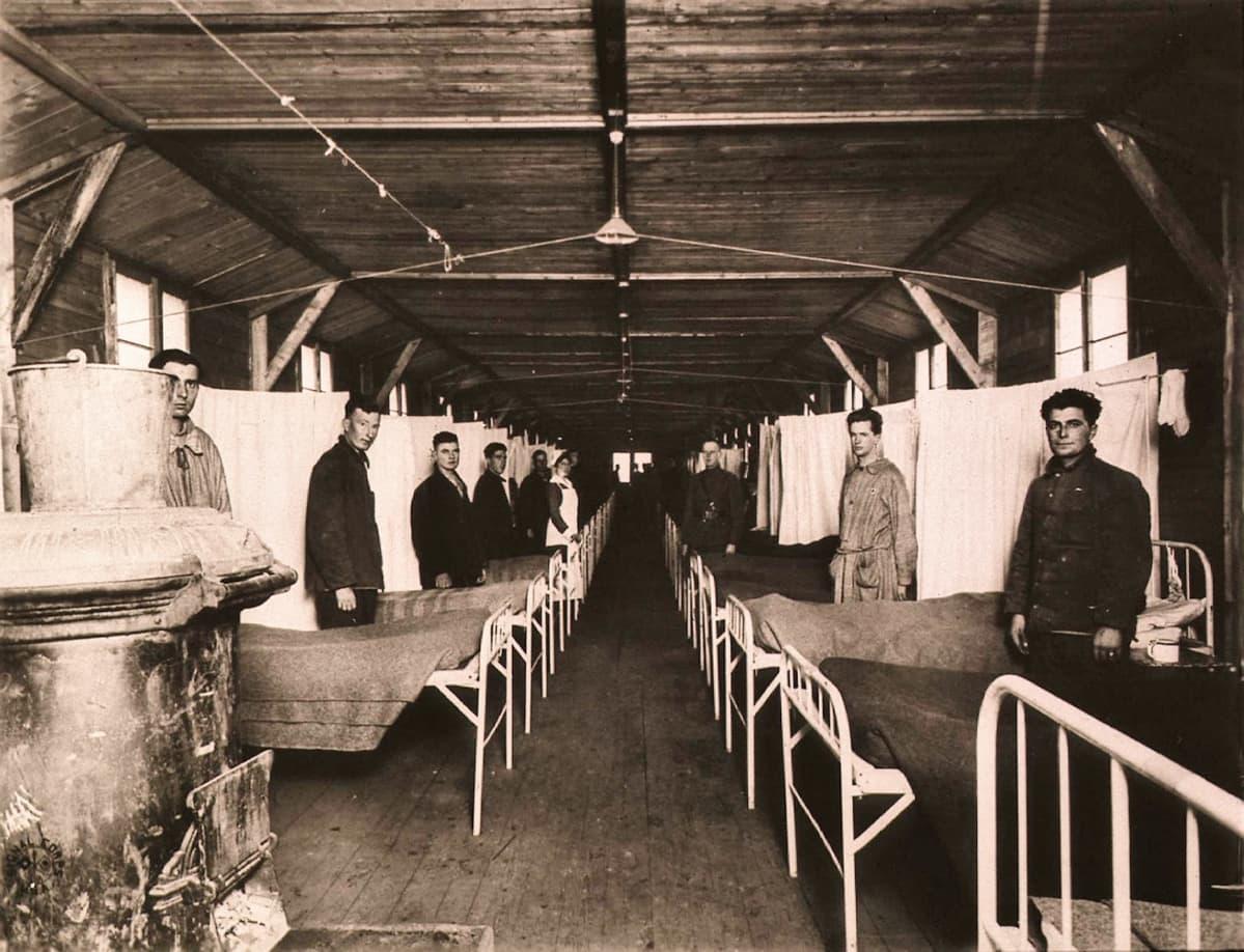 Mustavalkoinen kuva, jossa sairaalasänkyjen jono ja sänkyjen vieressä miehiä univormuissa.