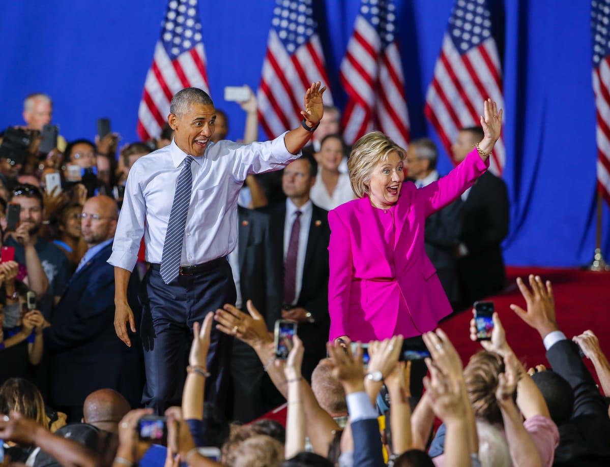 Demokraattien presidenttiehdokas Hillary Clinton pitää kampanjatilaisuuttaan yhdessä presidentti Barack Obaman kanssa. Charlotte, Pohjois-Carolina 5.7. 2016. Kuvassa parivaljakko vilkuttaa kansalle innokkaan ja vekkulin näköisinä.Taustalla liehuvat Yhdysvaltain liput.