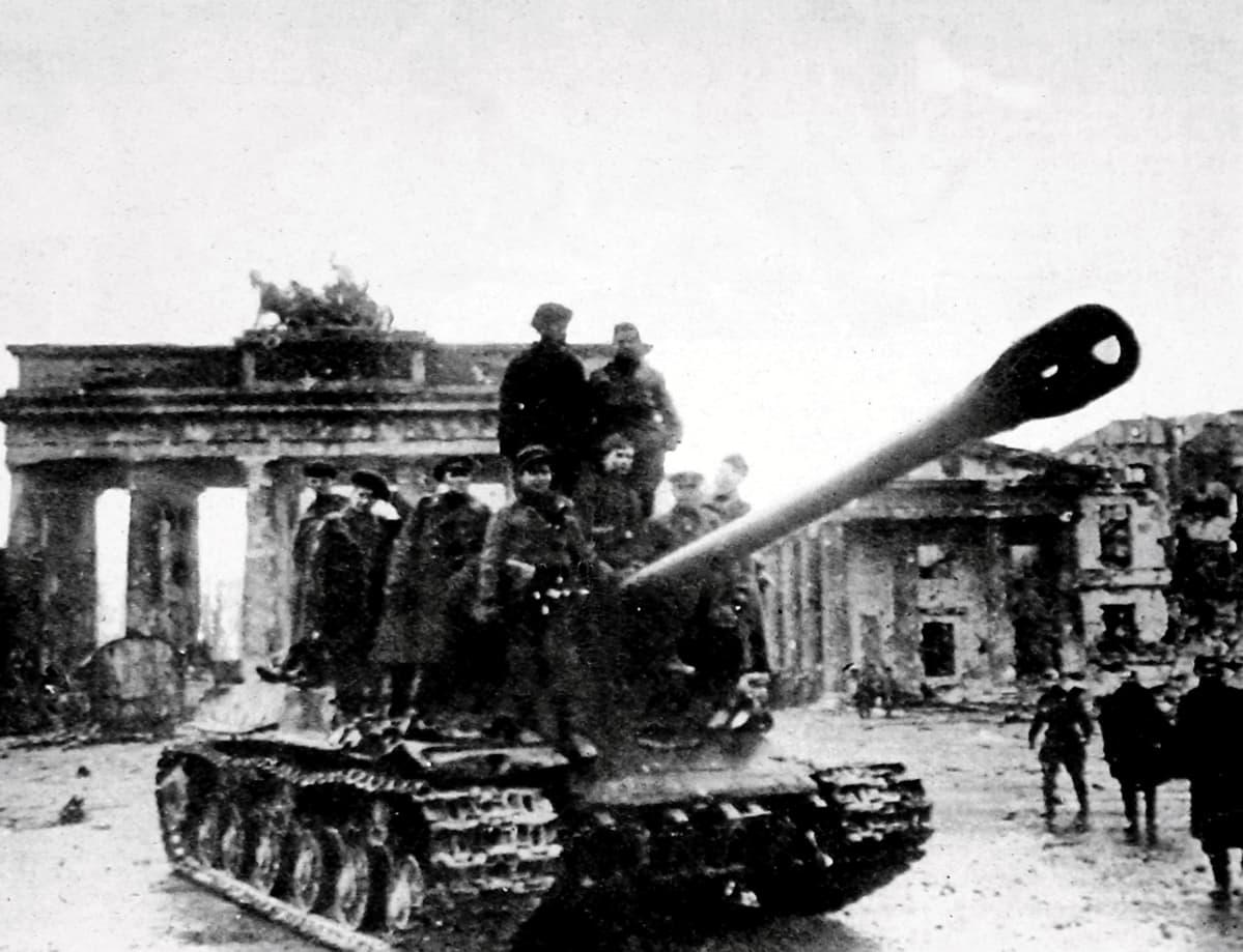 Neuvostojoukkojen panssarivaunu ajaa Berliinissä. Taustalla näkyy Brandenburgin portti. Vaunun päällä on sotilaita.